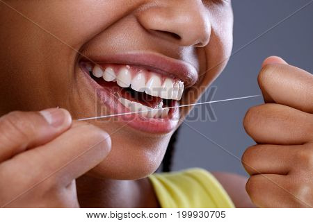 Afro-American female cleaning teeth using dental floss