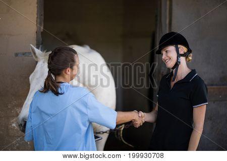 Female jockey giving handshake to vet by horse at barn