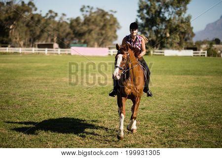 Full length of female jockey horseback riding on field at paddock