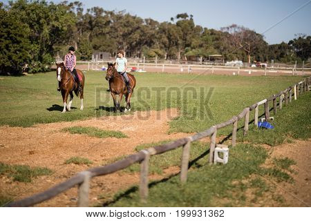 Mid distant view of female friends horseback riding on field during sunny day