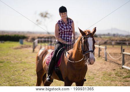 Portrait of smiling jockey horseback riding at paddock