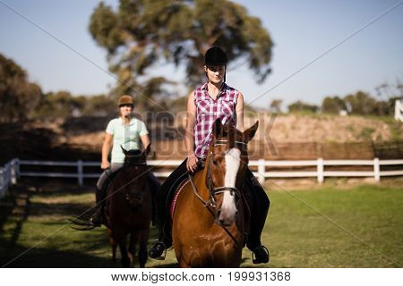 Females horseback riding on field during sunny day