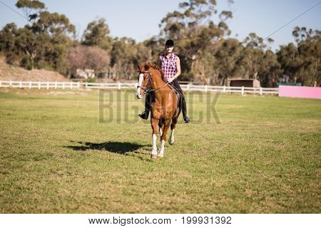 Full length of female jockey horseback riding on field during sunny day