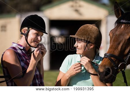 Smiling female friends talking with fastening helmet during horseback riding