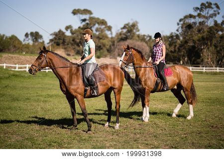 Young Women horseback riding on field during sunny day