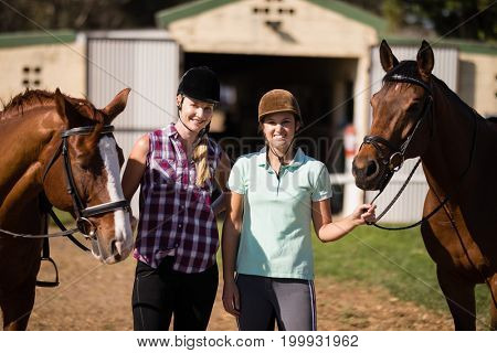 Portrait of smiling friends with horses standing on field at paddock