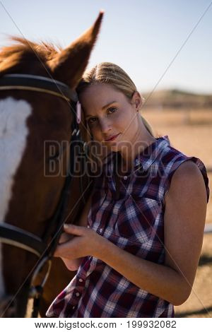 Portrait of young female standing by horse on field during sunny day