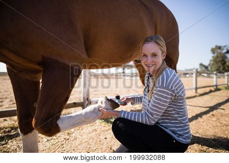 Portrait of female attaching horse shoe while crouching on field