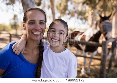 Close up portrait of smiling sisters with horse in background