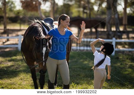 Sisters giving high five while standing by horse at paddock