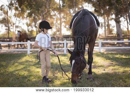Full length of girl wearing helmet standing by horse on field in paddock