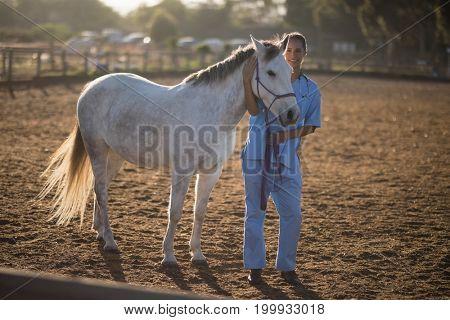Full length portrait of vet standing by horse at paddock