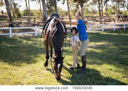 Portrait of siblings standing by horse on field at paddock