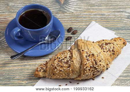Croissant with flax seeds and cup of hot coffee for breakfast on old wooden table
