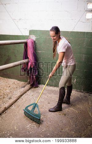 Full length of female jockey cleaning stable