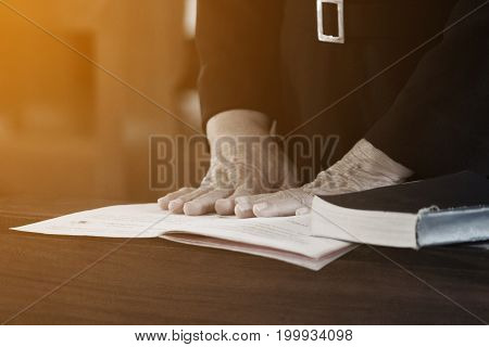 Woman hand placed on the bible pray to god. (prayer)