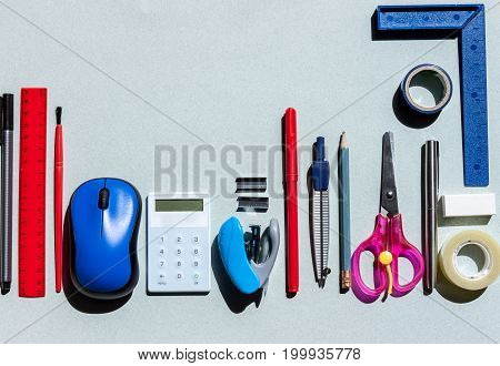 school stationery on blue paper background with copyspace