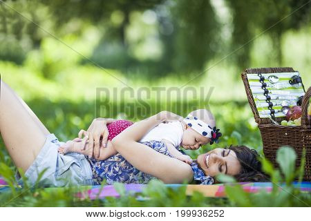 Young Mother Playing With Baby On Blanket In The Park