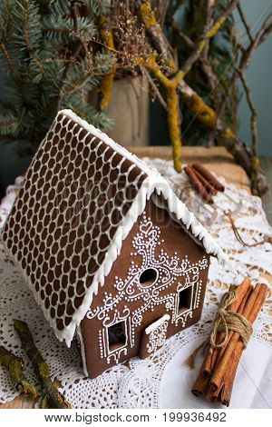 Gingerbread house, homemade, with Christmas tree in background, vertical