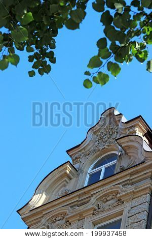 decorative gable of a baroque house with window blue sky green leaves