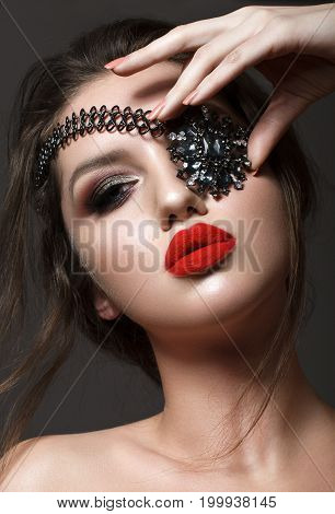 Beautiful young model with professional make up with red lips and smoky eyes