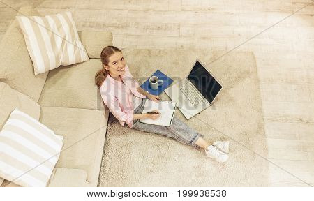 Top view of young pretty girl studying at home. Attractive female student sitting on carpet at living room, making notes.