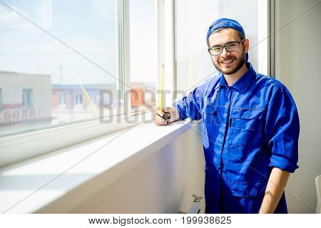 Construction worker installing window in a house