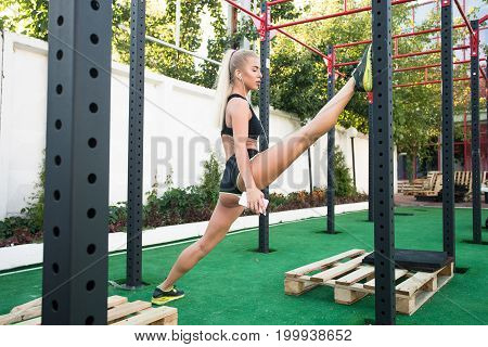 Training body to perfection. Beautiful bond girl stretches a twine on a sports ground with telephone and headphones. Twine of beautiful and sexy girl.