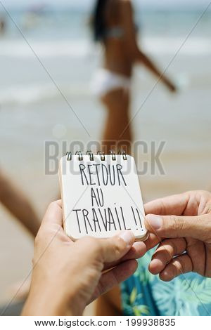 closeup of a young man sitting in a deck chair in the seashore of a beach showing a spiral notepad with the text retour au travail, back to work in French, handwritten in it