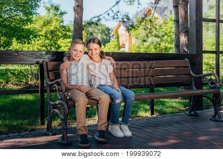 Kids Sitting On Bench In Park
