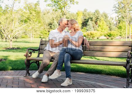 senior couple holding hands while resting on bench together in park