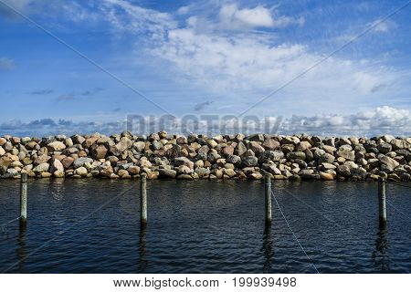 Breakwater at the marina in Helsingor Denmark with moorings and clouds in the blue sky