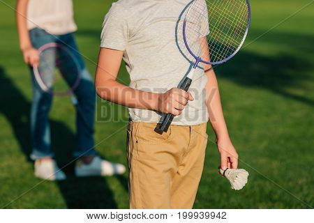 partial view of child holding badminton racket and shuttlecock in hands