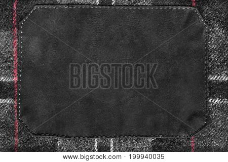 Blank black clothes label on gray plaid wool as a background