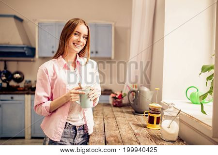 Young girl standing with cup of tea close to window in the kitchen. Female staying at home, looking through window, thinking and enjoying cup of tea.