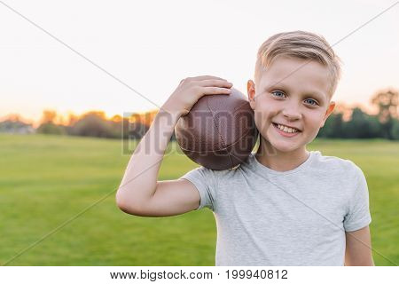portrait of preteen boy holding rugby ball and looking at camera in park