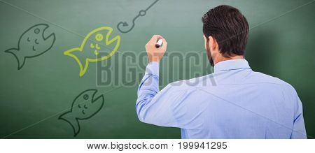 Businessman in suit writing with marker against green chalkboard