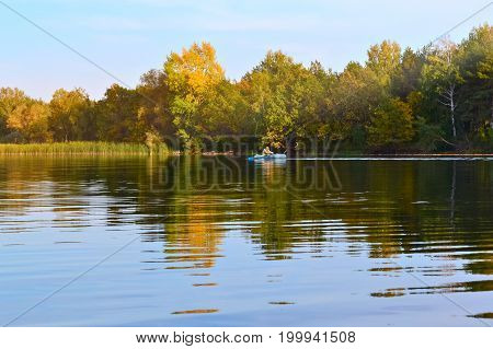 Autumn river landscape with a boat in the distance