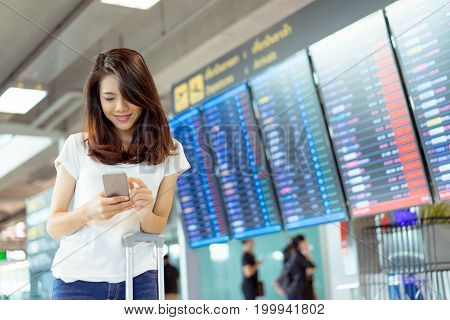 Young girl asian traveler using mobile smartphone with carrying hold suitcase luggage and passenger for tour travel booking ticket flight in airport international vacation time in holiday relaxation.