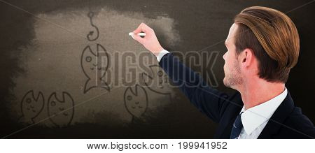 Well dressed businessman writing with chalk against blackboard