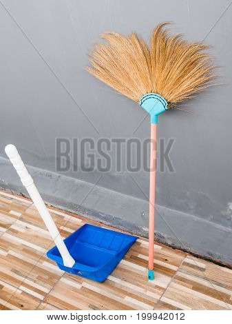 New broom and plastic dustpan near the house wall for working in the modern house.