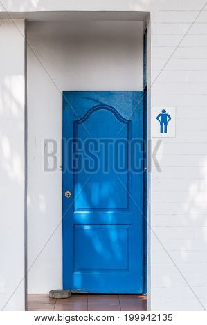 Public toilet with the blue wooden door is opened for the people in the urban park.