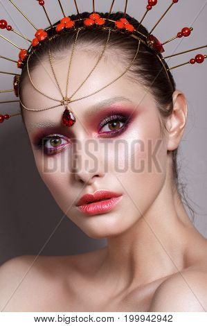 Fashion portrait of beautiful young model with professional purple makeup, perfect skin and unusual indian accessory on her head.