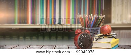 School supplies on desk against volumes of books on bookshelf