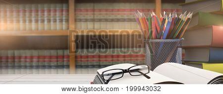 School supplies on desk against volumes of books on bookshelf in library