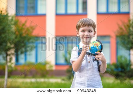 Portrait Of A Little Boy Holding A Globe. Travel Concept