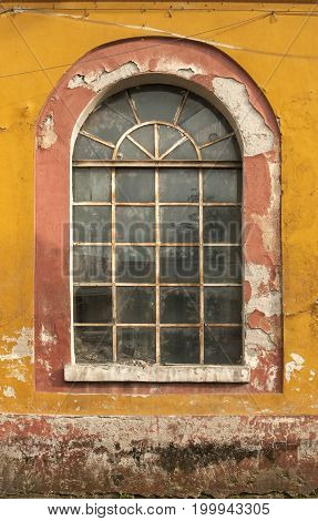 Old vintage weathered crumbling grunge glass window of abandoned industrial building