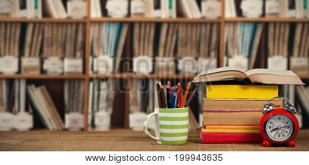 Stack of books by mug with colored pencils and alarm clock on wooden table against various multi colored books on shelf