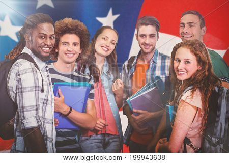Smiling group of students holding folders against american flag with stripes and stars