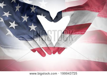 Woman making heart shape with hands against full frame of wrinkled american flag